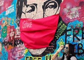 Photo d'arts et graffitis sur un mur extérieur : un masque rouge géant sur un visage géant portant des lunettes avec le mot « Love », « Hong Kong », etc. Une jeune femme à côté pose avec un masque et des lunettes de soleil.