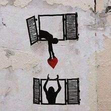 Dessin, sur un mur extérieur, d'un homme tendant un coeur par sa fenêtre vers une femme à une fenêtre plus bas.