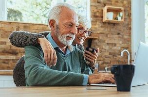Photo d'un couple d'environ 60 ans regardant ensemble un ordinateur portable, dans une belle cuisine ensoleillée. Un monsieur à la barbe blanche et, derrière lui, une dame souriante tenant une tasse.
