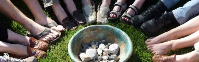 Photo où on voit 9 pairs de pieds de gens entourant un pot dans lequel il y a plusieurs cailloux.