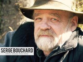 Portrait de Serge Bouchard : regard sympathique, chapeau beige contre le soleil, barbe blanche, manteau d'automne.
