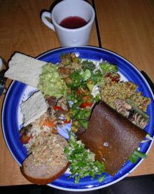 Photo d'un beau repas dans une assiette : un mélange de pains bruns, de salades, etc.