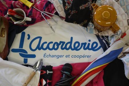 Logo entouré de petits objets : vêtements, crayons, micro, parapluie, etc. Le logo se lit « L'Accorderie, échanger et coopérer ». Le L est un noeud de cordes.