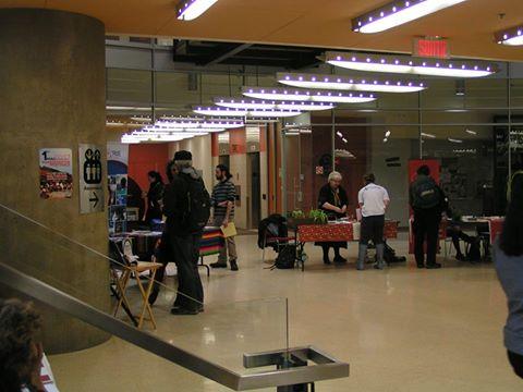 Photo : une partie du grand espace circulaire. Trois kiosques : Accorderie, CESIQ, etc. Des gens discutent ici et là.