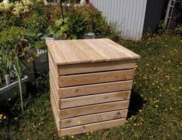 Photo : boîte en bois blancs sur du gazon près d'un jardin de maison.