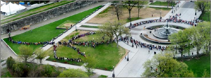 Photo du ciel: autour de la fontaine devant le parlement, des centaines de participants forment une ligne dessinant le logo du Collectif