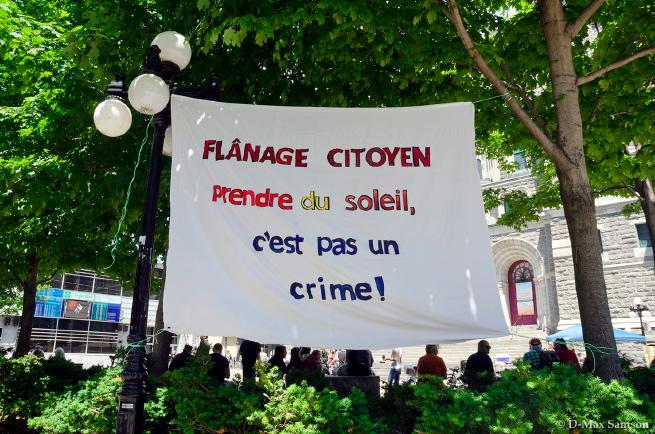 Banderole sur fond d'arbres verts du parvis St-Roch : Flânage citoyen - Prendre du soleil, c'est pas un crime.