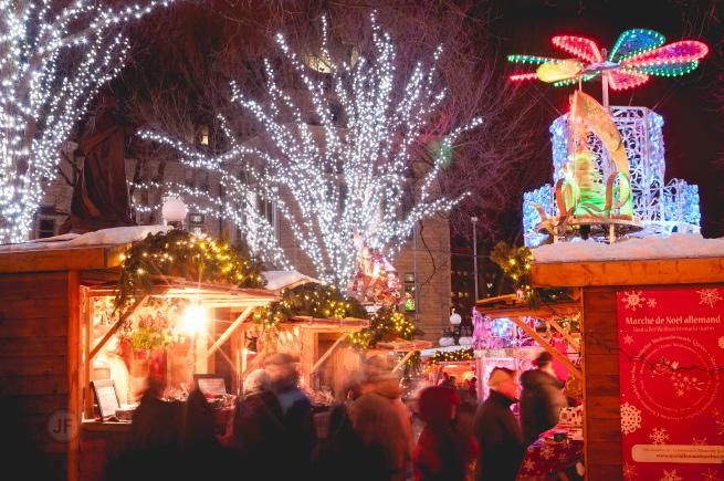 Photo de soir : arbres remplis de lumières blanches ; cabanes en bois bien éclairées ; affiche rouge du Marché de Noël allemand