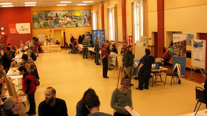 Photo de la salle sur la longueur : environ 20 kiosques, les gens discutent, belle peinture colorée au fond.