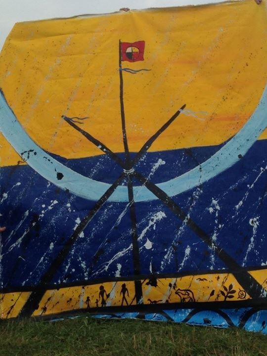 Peinture sur toile : ciel orange, sol orange avec petits personnages noirs, art autochtones, sur fond bleu marin comme une tempête. Un rayon bleu ciel courbe à travers la toile. Trois tiges forment un tipi géant au milieu de la toile, surmonté d'un drapeau rouge de la Première Nation : cercle divisé en quatre. - artiste atikamekw Jacques Newashish