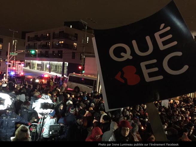Photo prise lors de l'événement: foule sur le Chemin Sainte-Foy la nuit. Une affiche noire carrée écrit QUÉ-BEC, mais le b est un coeur rouge brisé. Publiée par Irene Lumineau sur l'événement Facebook.