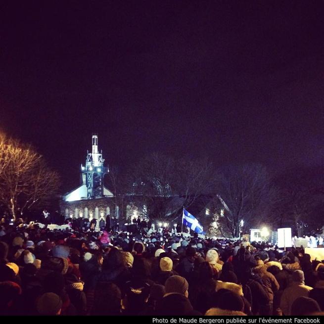 Photo prise lors de l'événement: grande foule la nuit, derrière l'église illuminée de loin. Un drapeau du Québec géant dans la foule plus loin. Publiée par Maude Bergeron sur l'événement Facebook.