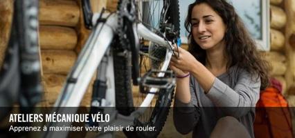 Photo : une jeune femme aux cheveux long brun-roux travaille sur un vélo argenté. Maison en bois ronds derrière.