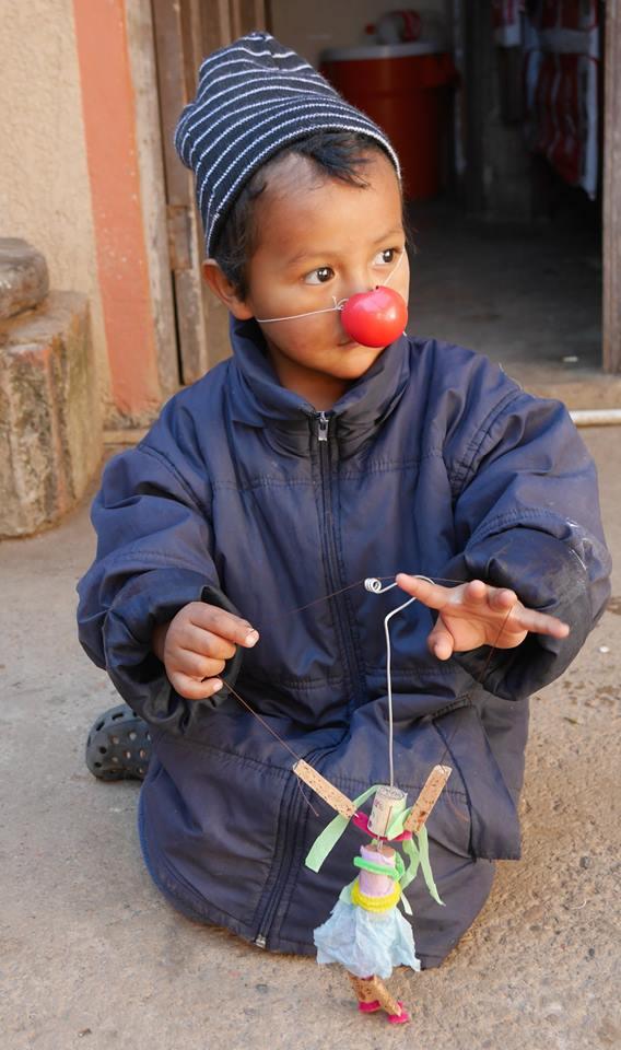 Belle photo d'un enfant, portant un nez rouge de clown, et jouant avec une marionnette fabriquée à la main. Le sol est de terre glaise. L'enfant porte une tuque rayée noire/blanche et un grand manteau d'hiver bleu-mauve (donc probablement dans une région montagneuse de l'Amérique du Sud).
