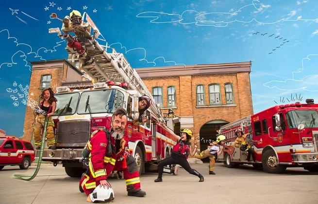 Image thématique pour Les Veillées dans Saint-Sauveur : des pompiers ici et là, incarnés par les artistes, devant une caserne. Deux camions de pompiers agrémentent le tout. Le ciel est dessiné à la main.