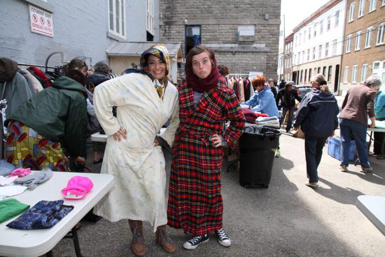 Photo : au soleil derrière l'église, deux participantes posent, avec des expressions exagérées et comiques, en robe de chambre. Plusieurs personnes derrière s'affairent aux tables.