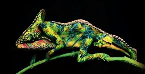 Deux personnes renversées une contre l'autre sont transformées en caméléon aux diverses texture d'écailles vertes. L'illusion est parfaite.