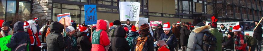 On voit un rassemblement coloré de gens, l'hiver, dont un Père Noël. On les voit surtout de dos devant un hôtel de Ste-Foy.