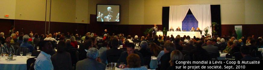 Congres des coop et mutualité sur le projet de société, sept. 2010 - Photo où on voit la grande salle de conférence remplie de gens assis à des tables, avec un écran géant montrant un homme parlant au micro [Palais des congrès de Lévis]