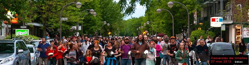 foule marchant sur la 3e Ave. de Limoilou vers vous: beaucoup d'adultes et d'enfants, casseroles à la main. Beaux arbres verts derrière.