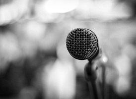 Photo d'un micro métallique gris vu du côté de la grille pour parler ; l'arrière est floue et blanc.