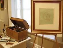 Photo : un coffre en bois, des outils de peinture, un cadre avec un petit dessin d'un visage au milieu.