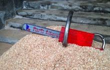 Photo : une fausse scie à chaîne rouge sur un tas de brans de scie. La lame porte les mots Parti Libéral avec son logo.