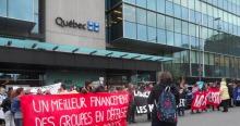 Photo : devant le ministère, sur le Québec on voit le drapeau du Québec, une foule de gens se tiennent en ligne unie avec des bannières, dont la plus lisible dit: Un meilleur financement des groupes en défense collective des droits.