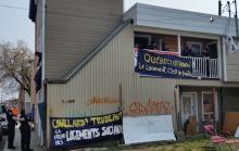 Photo : côté d'une habitation, surtout couverte de tolle beige, avec deux bannières: Couillard Trudeau il faut des logements sociaux ; Québec Ottawa : le logement, c'est un droit. Les squatteurs sont visibles de loin sur la galerie au haut. Un policier et une policière sont à l'entrée et regardent vers le haut.