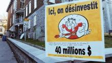 Photo de bas en haut de la rue Sainte-Claire.  Non loin de l'entrée du bâtiment où est le ComPop, une affiche sur fond jaune avec le dessin comique d'un homme se serrant la ceinture à excès. Ici, on désinvestit. 40 millions.