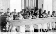 Photo ancienne de jeunes filles autochones dans une école catholique. Sous-titre: Le temps d'étude à l'école résidentielle Natale, (Le Fort) la Résolution, NWT. Crédit: biblio. et Archives le Canada, ID PA-042133.