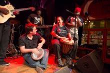 Photo : cinq personnes sur une petite scène. Éclairage rouge. Un jeune homme à la peau pâle joue du tam tam. Une dame plus âgée à la peau foncée joue aussi du tam tam avec lui. Un chanteur les accompagne, un bassiste et un guitariste, tous à la peau foncée d'origine africaine.