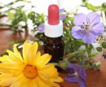 Photo vue de près d'une petite bouteille munie d'un compte-goutte, entourée de deux fleurs, une jaune et une mauve.