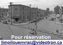 Photo en noir et blanc d'une artère principal de Limoilou jadis : rues larges, poteaux de téléphone, grand écriteau rond « White Rose », quelques piétons.