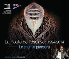 Affiche officielle « Route de l'esclavage : 1994-2014 - Le chemin parcouru - Un crime contre l'humanité » : sculpture d'un simple bateau en bois, mais rempli au fond d'esclaves Africains ; le tout placé sur un tas de branches d'arbres africains. Logo de l'UNESCO. Photo de M. Moussa Ali, plume à la main à son bureau.