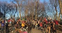 Photo d'une foule d'environ 30 cyclistes, côte-à-côte pour la photo, près de grands arbres vers la fin de l'hiver au soleil.  Certains tiennent bien haut leur vélo.