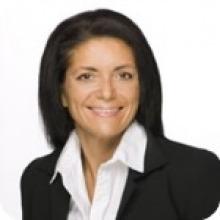 Photo professionnelle de Nathalie Lamarre. Souriante, cheveux noirs, veston noir sur chemise blanche.
