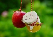 Une pomme et un pot de compotte suspendus à deux petits cordes.