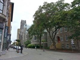Photo : à partir du coin de rue, le Presbytere, deux arbres verts devant, l'église au loin ; à gauche, le magasin Laliberté. La rue est fait de briques.
